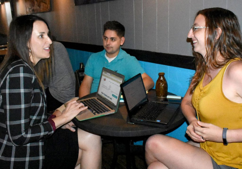 Kate Greene, managing principal of Mountain Town Strategies, at left, talks with Anna Hicks, county captain of Marion County Can't Wait, at right, while member Mike White listens at a recent planning session at Joe N'Throw on Adams Street in Fairmont.